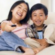 Two youngchildren in living room with remote control smiling — Stok fotoğraf