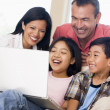 Family in living room with laptop smiling — Stock Photo #4768602