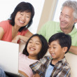 Couple with two young children in living room with laptop smilin - Stock Photo
