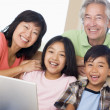 couple with two young children in living room with laptop smilin — Stock Photo