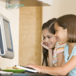 Two young girls in kitchen with computer smiling — Stock Photo