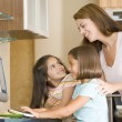 Stock Photo: Womand two young girls in kitchen with computer smiling