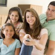 Family in living room with remote control smiling — Lizenzfreies Foto
