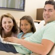 Royalty-Free Stock Photo: Family in living room with laptop smiling