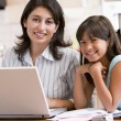 Woman and young girl in kitchen with laptop and paperwork smilin — Stock Photo #4768637