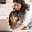 Stock Photo: Womand young girl in kitchen with laptop and paperwork smilin