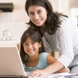 Stock Photo: Woman and young girl in kitchen with laptop and paperwork smilin