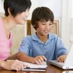 femme aidant le jeune garçon avec ordinateur portable faire ses devoirs dans la salle à manger s — Photo