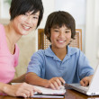 Stock Photo: Womhelping young boy with laptop do homework in dining room s