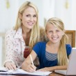 Woman helping young girl with laptop do homework in dining room — Stock Photo
