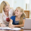 Stock Photo: Womhelping young girl with laptop do homework in dining room