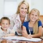 donna aiutando due bambini piccoli con laptop faccia compiti in dini — Foto Stock