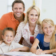 Couple helping two young children with laptop do homework in din — Stock Photo #4768690