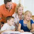 Stock Photo: Couple helping two young children with laptop do homework in din