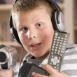 Young boy wearing headphones in bedroom holding many electronic — Stock Photo #4768692