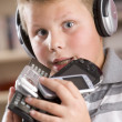 Royalty-Free Stock Photo: Young boy wearing headphones in bedroom holding many electronic
