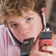 Young boy in bedroom holding many cellular phones - Stock Photo