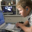 Young boy in bedroom using laptop and listening to MP3 player - Stock Photo