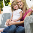 Woman and young girl sitting on patio laughing - Stock Photo