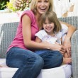 Woman and young girl sitting on patio laughing — Stock Photo #4768716