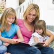 Woman and two young girls sitting on patio reading book smiling — Stock Photo