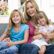 Woman and two young girls sitting on patio smiling — Stock Photo