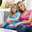 Woman and young girl sitting on patio smiling — Stock Photo #4768729