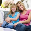 Woman and young girl sitting on patio smiling — Stock Photo