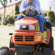 Man outdoors on lawnmower smiling — Stock Photo #4768750
