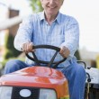 Man outdoors driving lawnmower smiling — Stock Photo