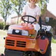 Woman outdoors driving lawnmower smiling — Stock fotografie