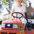 Woman outdoors driving lawnmower smiling — Stockfoto