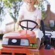 На открытом воздухе вождения газонокосилку улыбается женщина — Стоковое фото