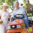 Couple outdoors with tools and lawnmower smiling — Stock Photo #4768760