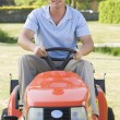 Man outdoors driving lawnmower smiling — Stock Photo #4768793