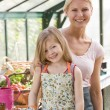 Young girl and woman in greenhouse smiling - 图库照片