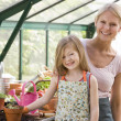 Stock Photo: Young girl and womin greenhouse smiling