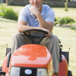 Man outdoors on lawnmower smiling — Stok fotoğraf
