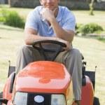 Человек на открытом воздухе на газонокосилку улыбается — Стоковое фото