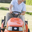 Man outdoors driving lawnmower — Stok fotoğraf