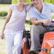 Couple outdoors with lawnmower smiling — Stock Photo #4768834