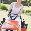 Woman outdoors driving lawnmower smiling — Stock Photo