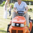 Man outdoors driving lawnmower smiling with family in background — Stock Photo #4768839