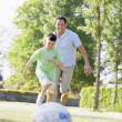 Man and young boy outdoors playing soccer and having fun — Stock Photo