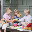 Three young children in shed playing tea and smiling — Stock Photo