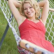 Stock Photo: Womrelaxing in hammock smiling