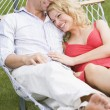 Couple relaxing in hammock smiling - Stock Photo