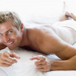 Man lying in bed pointing and smiling — Stock Photo #4768902