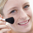 Woman with makeup brush smiling - Foto Stock