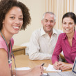 Doctor with laptop and couple in doctor's office smiling — Stock Photo